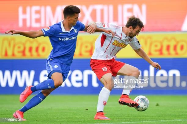 Benedikt Gimber of Regensburg is challenged by Mathias Honsak of Darmstadt during the Second Bundesliga match between SSV Jahn Regensburg and SV...