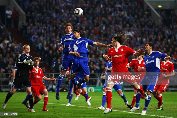 Benedikt Hoewedes and Carlos Zambrano of Schalke jump for a header during the DFB Cup semi final match between FC Schalke 04 and FC Bayern Muenchen...