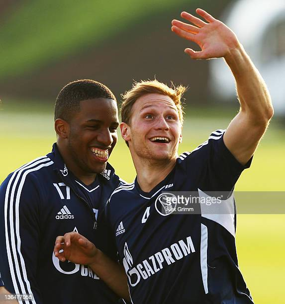Benedikt Hoewedes and Jefferson Farfan laugh during a training session of Schalke 04 at the ASPIRE Academy for Sports Excellence on January 6 2012 in...