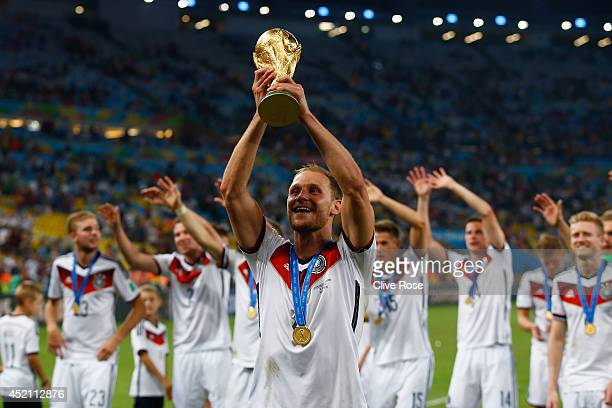 Benedikt Hoewedes celebrates with the World Cup trophy after defeating Argentina 1-0 in extra time during the 2014 FIFA World Cup Brazil Final match...