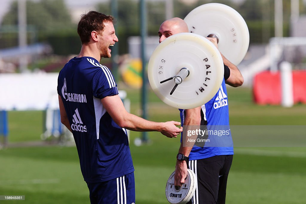 Benedikt Hoewedes laughs with athletics coach Ruwen Faller during a Schalke 04 training session at the ASPIRE Academy for Sports Excellenc on January 4, 2013 in Doha, Qatar.