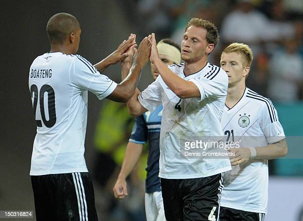 Benedikt Hoewedes of Germany celebrates with teammate Jerome Boateng after scoring his team's first goal during the international friendly match...