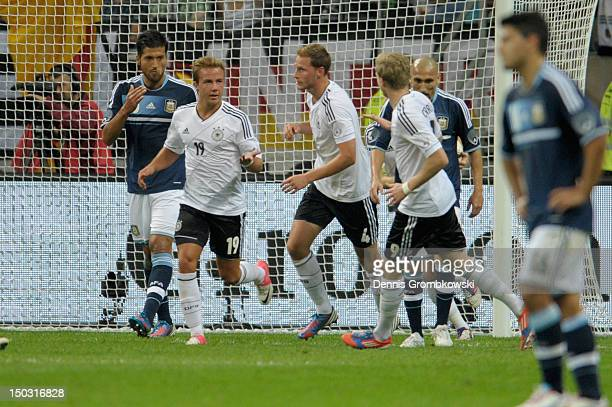 Benedikt Hoewedes of Germany celebrates with teammate Mario Goetze after scoring his team's first goal during the international friendly match...