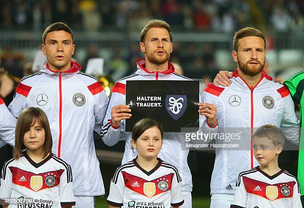 Benedikt Hoewedes of Germany holds a sign reading 'Haltern mourn' in relation to the recent Germanwings air crash alongisde Jonas Hector and Shkodran...