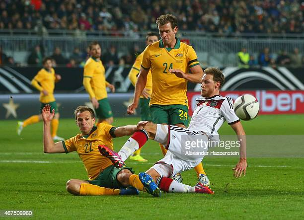 Benedikt Hoewedes of Germany is challenged by Alex Wilkinson and Luke DeVere of Australia during the international friendly match between Germany and...