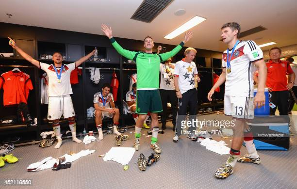 Benedikt Hoewedes of Germany Manuel Neuer of Germany and Thomas Mueller of Germany celebrate in the Germany dressing room after the 2014 FIFA World...