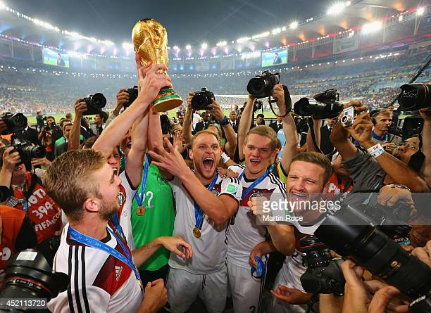 Benedikt Hoewedes of Germany raises the World Cup trophy with teammates after defeating Argentina 1-0 in extra time during the 2014 FIFA World Cup...