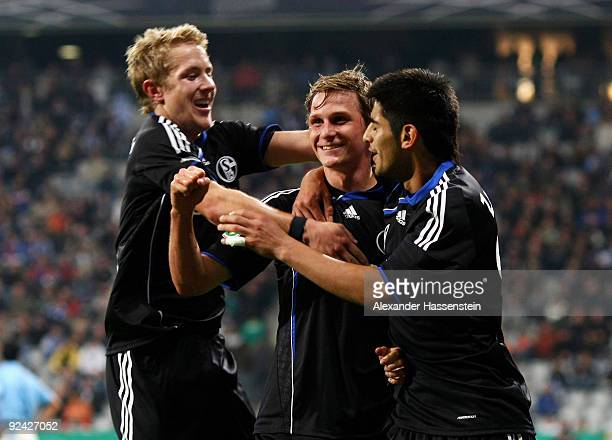 Benedikt Hoewedes of Schalke celebrates after scoring his team's third goal with team mates Lewis Holtby and Carlos Zambrano during the DFB Cup round...