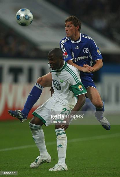 Benedikt Hoewedes of Schalke challenges Grafite of Wolfsburg during the Bundesliga match between FC Schalke 04 and VfL Wolfsburg at Veltins Arena on...