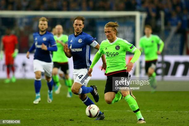 Benedikt Hoewedes of Schalke challenges Kasper Dolberg of Amsterdam during the UEFA Europa League quarter final second leg match between FC Schalke...
