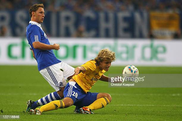 Benedikt Hoewedes of Schalke challengesTeemu Pukki of Helsinki during the UEFA Europa League play-off second leg match between FC Schalke and HJK...