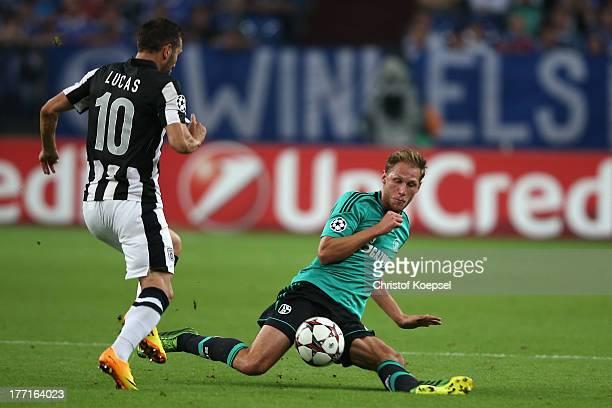 Benedikt Hoewedes of Schalke defends against Lucas Perez Martinez of Saloniki during the UEFA Champions League Playoff first leg match between FC...