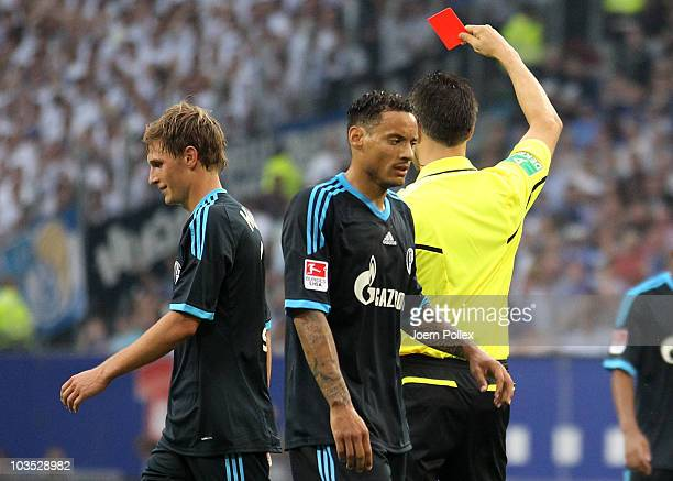 Benedikt Hoewedes of Schalke gets the red card from referee Wolfgang Stark during the Bundesliga match between Hamburger SV and FC Schalke 04 at...