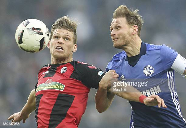 Benedikt Hoewedes of Schalke is challenged by Florian Niederlechner of Freiburg during the Bundesliga match between FC Schalke 04 and SC Freiburg at...