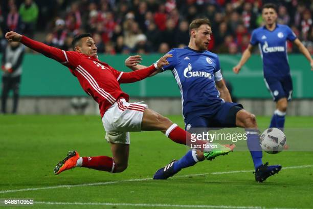 Benedikt Hoewedes of Schalke is challenged by Thiago Alcantara of Muenchen during the DFB Cup quarter final between Bayern Muenchen and FC Schalke 04...