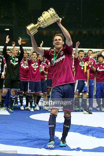 Benedikt Hoewedes of Schalke lifs the trophy after winning 50 the DFB Cup final match between MSV Duisburg and FC Schalke 04 at Olympic Stadium on...