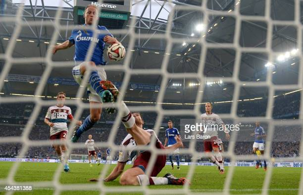Benedikt Hoewedes of Schalke scores his teams first goal past Xabi Alonso of Muenchen during the Bundesliga match between FC Schalke 04 and FC Bayern...