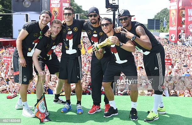 Benedikt Hoewedes Per Mertesacker Mesut Oezil Sami Khedira Lukas Podolski and Jerome Boateng celebrate during the German team victory ceremony on...