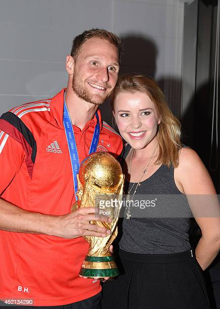 Benedikt Howedes of Germany and girlfriend Lisa Wesseler pose with the World Cup trophy as he celebrates with teammates at a party after winning the...