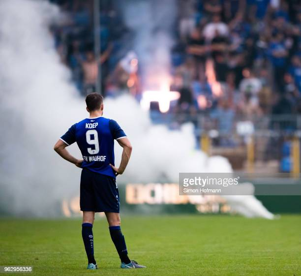 Benedikt Koep of Mannheimreacts as supporters of his team light fireworks during the Third League Playoff Leg 2 match between SV Waldhof Mannheim and...