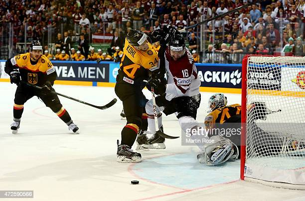 Benedikt Kohl of Germany and Kaspars Daugavins of Latvia battle for the puck during the IIHF World Championship group A match between Czech Republic...