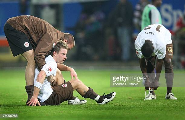 Benedikt Pliquett, Marvin Braun and Charles Takyi of St. Pauli sit dejected on the pitch during the 2nd Bundesliga match between VfL Osnabrueck and...