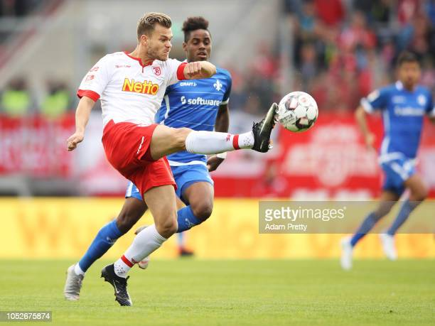 Benedikt Saller of Jahn Regensburg is challenged by Joevin Jones of SV Darmstadt 98 during the Second Bundesliga match between SSV Jahn Regensburg...