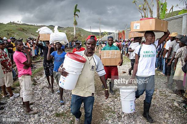 Beneficiaries carry their emergency kits including rice hygiene articles aquatabs for cholera prevention and plastic sheets on October 20 2016 in...