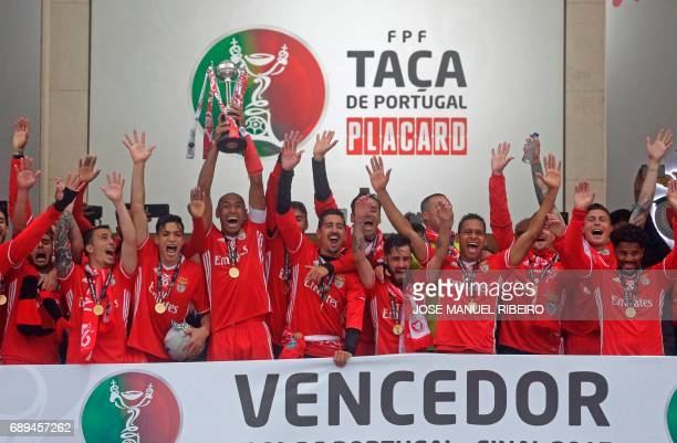 Benfica captain Brazilian defender Luisao holds up the trophy as he celebrates with teammates their victory at the end ofthe Portugal's Cup final...