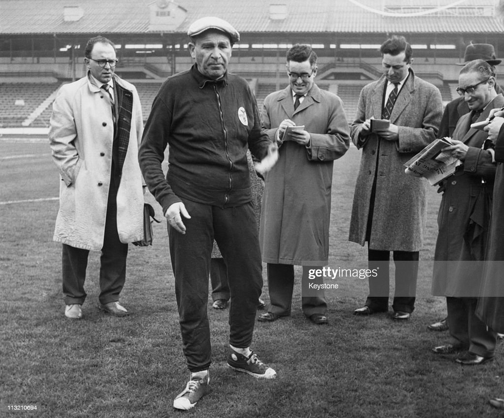 Benfica coach and manager Bela Guttmann (1900 - 1981) with a group of journalists at White City in London, 4th April 1962. He had just accused Tottenham Hotspur of watering the pitch at White Hart Lane, in preparation for their game against Benfica the next day. The match was the second leg semi-final of the European Cup.