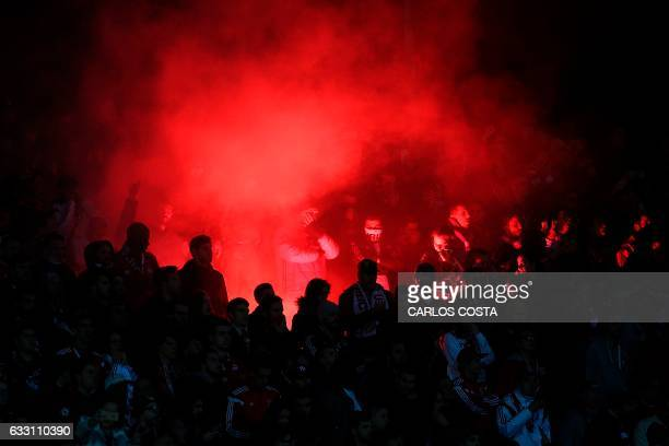 TOPSHOT Benfica fans light flares during the Portuguese league football match Vitoria Setubal vs SL Benfica at the Bonfim stadium in Setubal on...