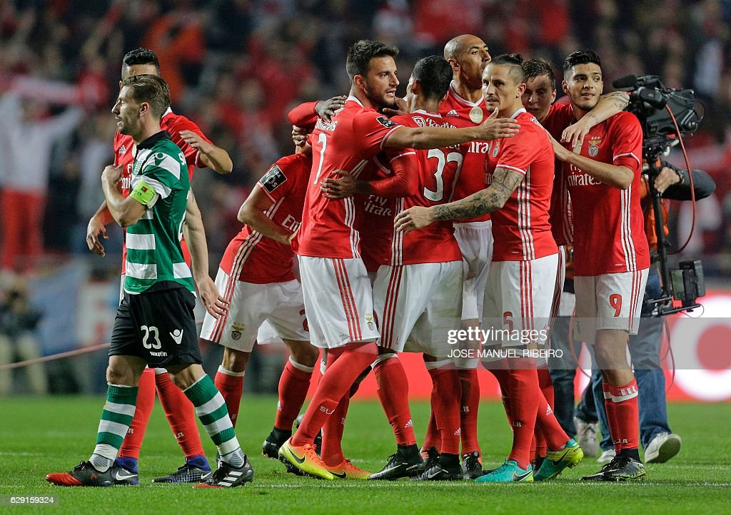 Benfica players celebrate their victory past Sporting's midfielder Adrien Silva at the end of the Portuguese league football match SL Benfica vs Sporting CP at the Luz stadium in Lisbon on December 11, 2016. / AFP / JOSE
