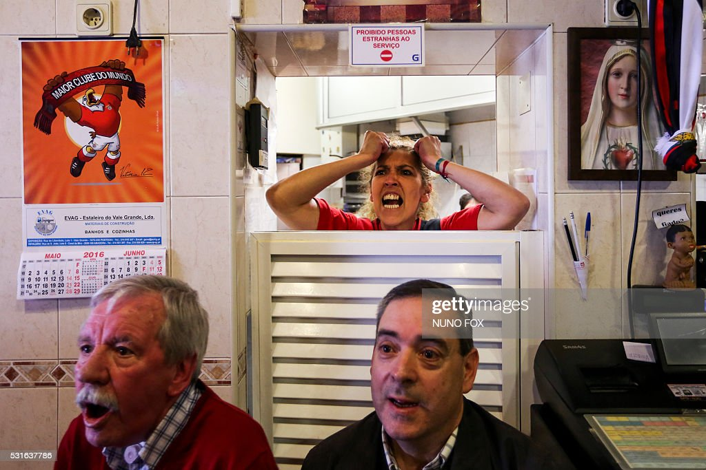 TOPSHOT - Benfica supporters watch the Portuguese League football match SL Benfica vs CD Nacional on television at 'A Ginginha' restaurant in downtown Lisbon on May 15, 2016. / AFP / NUNO FOX