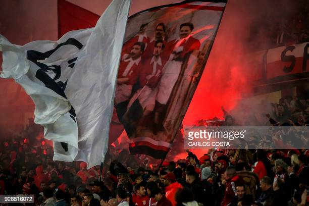 Benfica supporters wave flags during the Portuguese league football match between SL Benfica and CS Maritimo at the Luz stadium in Lisbon on March 3...
