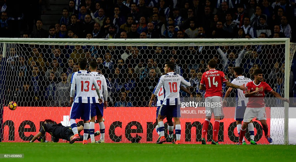 Benfica's Argentinian defender Lisandro Lopez (R) celebrates after scoring during the Portuguese league football match FC Porto vs SL Benfica at the Dragao stadium in Porto on November 6, 2016. The game ended with a draw 1-1. / AFP / MIGUEL