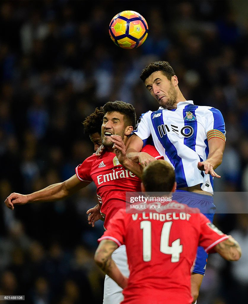 Benfica's Argentinian defender Lisandro Lopez (L) jumps for the ball with Porto's Spanish defender Ivan Marcano during the Portuguese league football match FC Porto vs SL Benfica at the Dragao stadium in Porto on November 6, 2016. / AFP / MIGUEL
