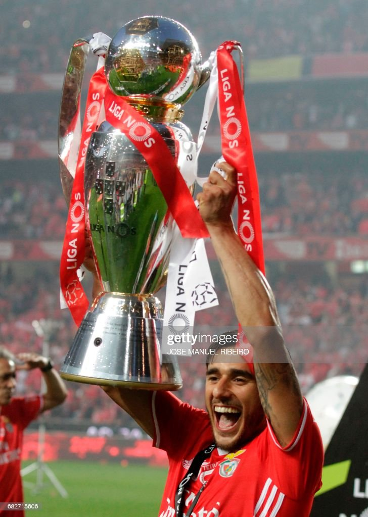 Benfica's Argentinian forward Eduardo Salvio holds the cup after winning their 36th title at the end of the Portuguese league football match SL Benfica vs Vitoria Guimaraes SC at the Luz stadium in Lisbon on May 13, 2017. Lisbon giants Benfica clinched a fourth straight Portuguese league title on May 13, 2017 with a 5-0 victory over Vitoria Guimaraes. The champions have an unassailable 81 points from 33 games and cannot be caught by Porto, who are eight points behind with just two games to play. /