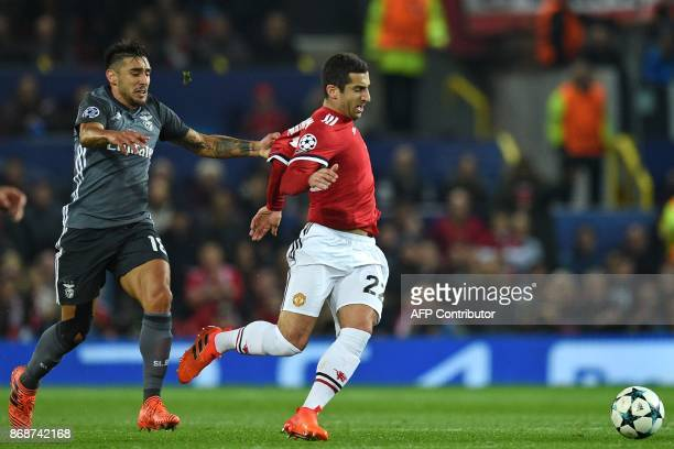 Benfica's Argentinian striker Eduardo Salvio is booked after pulling back Manchester United's Armenian midfielder Henrikh Mkhitaryan during the UEFA...