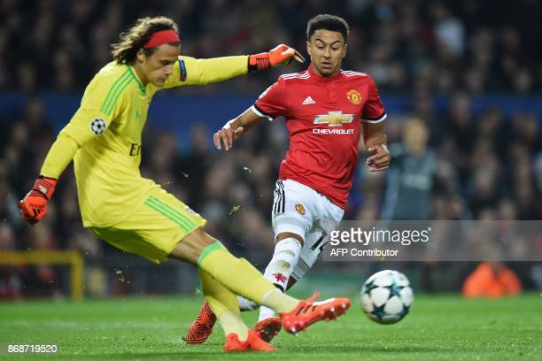 Benfica's Belgian goalkeeper Mile Svilar clears the ball under pressure from Manchester United's English midfielder Jesse Lingard during the UEFA...