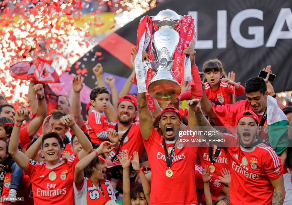 TOPSHOT - Benfica's Brazilian Defender and captain Luisao (L) holds the cup of the Portuguese league as he celebrates with his team after the football match SL Benfica vs CD Nacional at Luz stadium in Lisbon on May 15, 2016. /