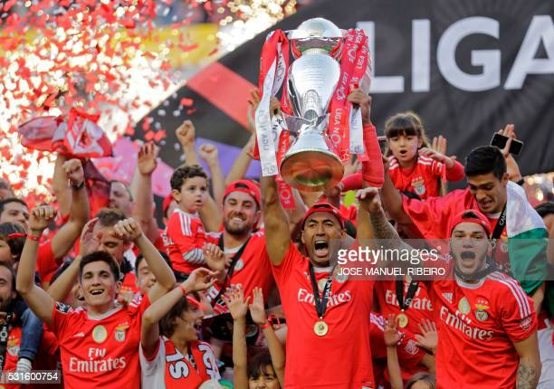 TOPSHOT Benfica's Brazilian Defender and captain Luisao holds the cup of the Portuguese league as he celebrates with his team after the football...