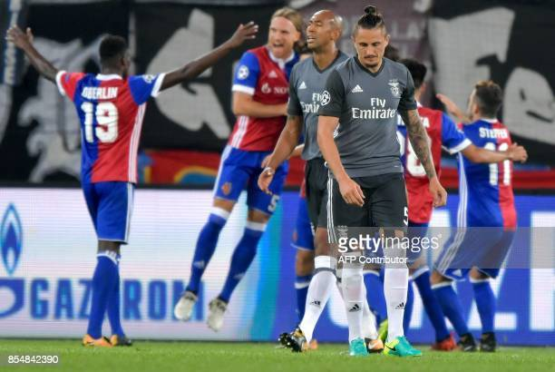 Benfica's Brazilian defender Luisao and Benfica's Serbian midfielder Ljubomir Fejsa wear dejected looks as Basel's players celebrate a goal during...