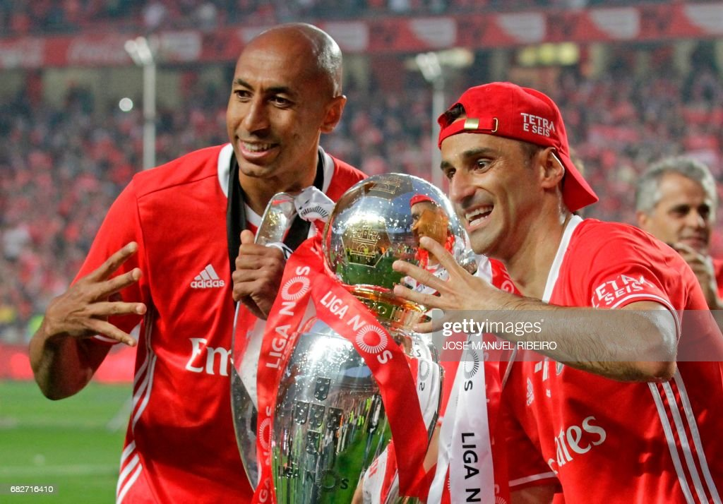 Benfica's Brazilian defender Luisao (L) and forward Jonas hold the cup after winning their 36th title at the end of the Portuguese league football match SL Benfica vs Vitoria Guimaraes SC at the Luz stadium in Lisbon on May 13, 2017. Lisbon giants Benfica clinched a fourth straight Portuguese league title on May 13, 2017 with a 5-0 victory over Vitoria Guimaraes. The champions have an unassailable 81 points from 33 games and cannot be caught by Porto, who are eight points behind with just two games to play. /
