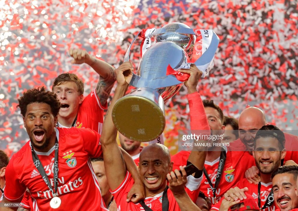 Benfica's Brazilian defender Luisao (C) holds the Portuguese League trophy past teammates as they celebrate winning their 36th title at the end of the Portuguese league football match SL Benfica vs Vitoria Guimaraes SC at the Luz stadium in Lisbon on May 13, 2017. Lisbon giants Benfica clinched a fourth straight Portuguese league title on May 13, 2017 with a 5-0 victory over Vitoria Guimaraes. The champions have an unassailable 81 points from 33 games and cannot be caught by Porto, who are eight points behind with just two games to play. /