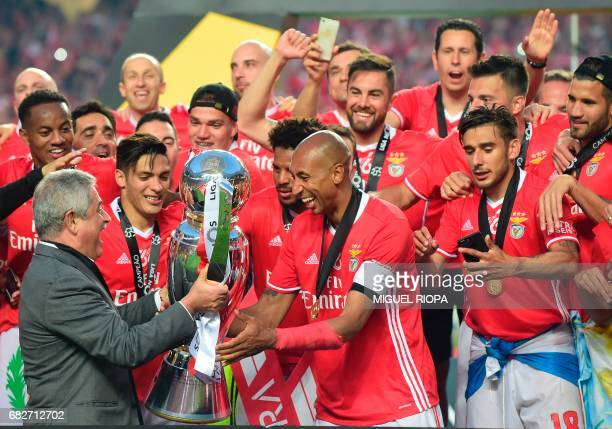 Benfica's Brazilian defender Luisao receives the Portuguese league's trophy from his president Luis Felipe Vieira after winning their 36th title at...