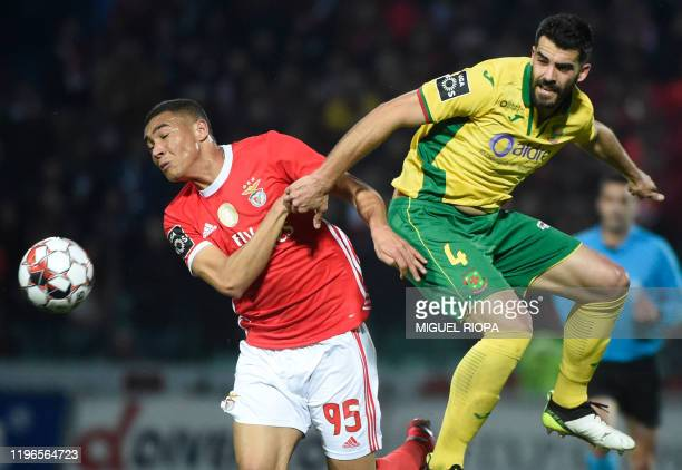 Benfica's Brazilian forward Carlos Vinicius vies with Pacos Ferreira's Portuguese defender Andre Micael during the Portuguese league football match...