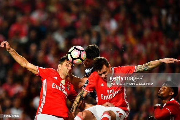 TOPSHOT Benfica's Brazilian forward Jonas Oliveira and Benfica's Swedish defender Victor Lindelof head the ball with Porto's Brazilian defender...