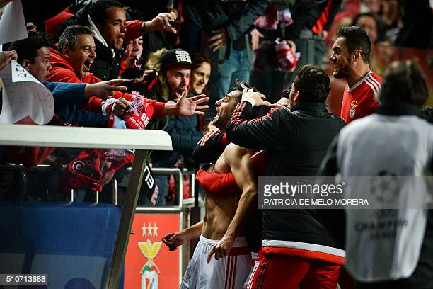 Benfica's Brazilian forward Jonas Oliveira celebrates with the supporters after scroing during the UEFA Champions League round of 16 football match...
