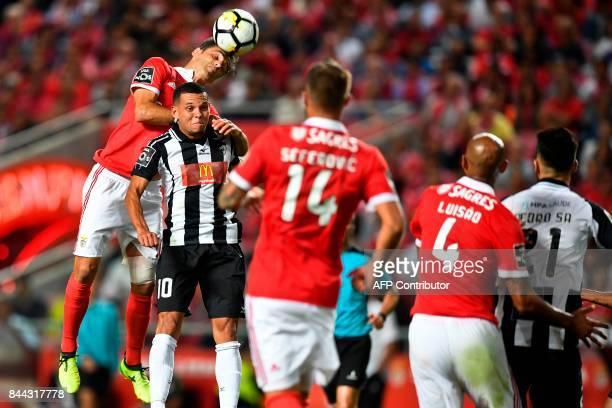 Benfica's Brazilian forward Jonas Oliveira heads the ball with Portimonense's Brazilian midfielder Ewerton Pereira during the Portuguese league...