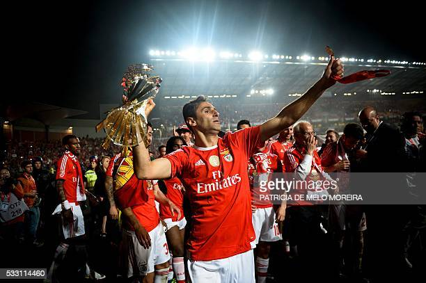 Benfica's Brazilian forward Jonas Oliveira holds the trophy as he celebrates after winning the Portuguese League Cup final football match CS Maritimo...